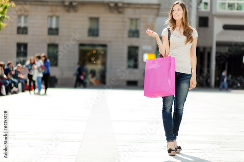 Young woman with shopping bags walking on the city street