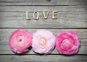 Ranunculus flowers and letters LOVE on wood
