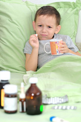 The boy is sick. Holding a pill and do not want to drink it