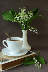 Bouquet of lilies of the valley, a book, a cup of coffee.