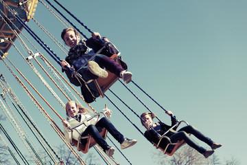 Teenage girls on the chain swing carousel