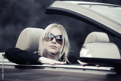 Young woman driving convertible car