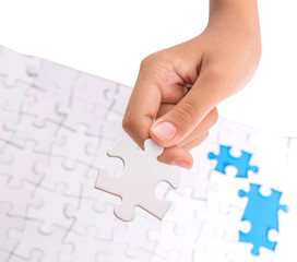 Young girl hand playing jigsaw puzzle