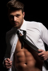Man in suit showing abs a result of hard workout