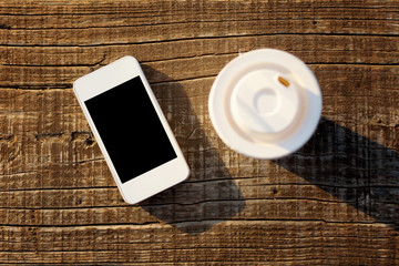 White smart phone and coffee cup on wooden surface