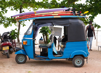 Blue tuk tuk vehicle transporting surfboards on the roof.