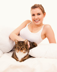 young womanwith cat  in her bed