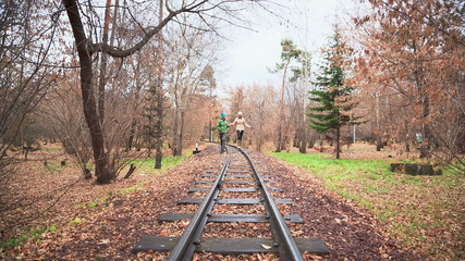 Walk Along The Rails, Man and Woman Walking in the Autumn Park