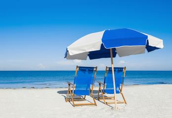 sun loungers and a beach umbrella on silver sand