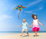 Fototapety Sister and brother playing with kite on beach