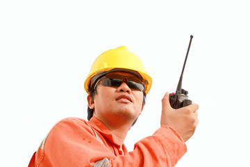 young man communicating on walkie-talkie at site
