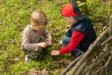 Two young boys lighting a small fire