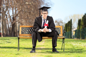 Male graduate sitting on bench and holding diploma