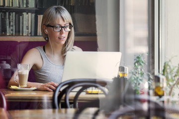 Young woman sitting in cafe and using laptop computer