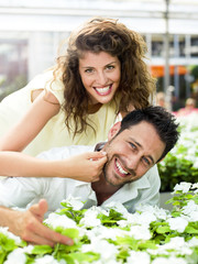 couple have fun choosing flower in a greenhouse