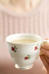 Woman holding china teacup of tea
