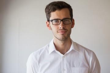 Casual businessman smiling at camera wearing glasses