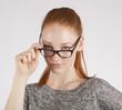 Junge, rothaarige Frau trägt Brille
