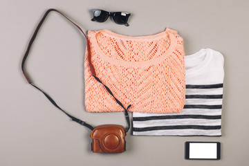 Summer outfit of hipster woman on grey background.