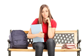 Female student contemplating seated on a bench