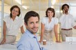 Smiling young businessman with colleagues at office