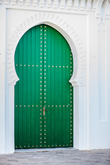 Massive green door in a white wall