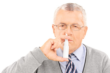 Senior man spraying medication in his nose