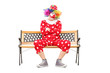 Unhappy clown sitting on a wooden bench