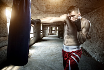 Young man boxing workout in an old building