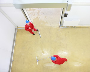 two workers cleaning floor in industrial building