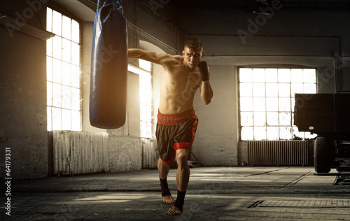 Fotobehang Vechtsporten Young man boxing workout in an old building