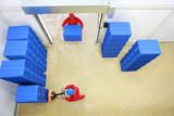 two workers working with plastic blue boxes in small warehouse