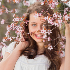 Girl with braces holding blossoming tree branch