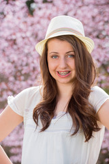 Girl with braces wearing hat spring blossom