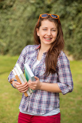 Cheerful student with braces holding books outside