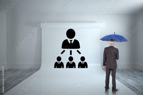 Composite image of businessman holding umbrella