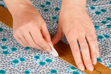the hands of tailor draw the pattern of clothing a chalk