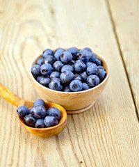 Blueberries in wooden bowl and spoon on board