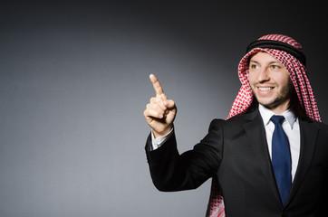 Arab businessman pressing virtual buttons against grey backgroun