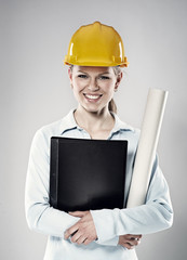 Woman constructor in helmet standing with project blueprints