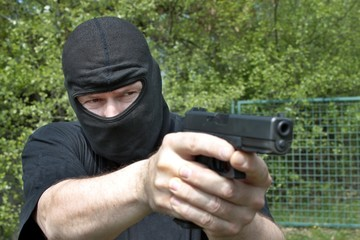 Masked man aims with gun
