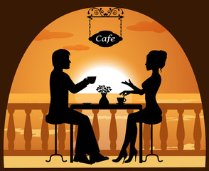 couple in a cafe on the beach at sunset