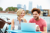 Young Couple Sitting On Roof Terrace Using Laptop