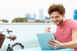 Young Man Sitting On Roof Terrace Using Digital Tablet