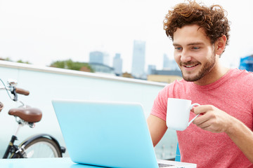 Young Man Sitting On Roof Terrace Using Laptop