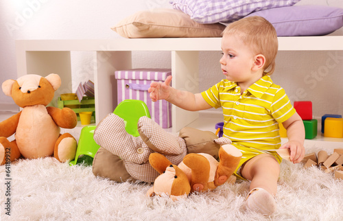Cute little boy with toys in room - 64189932