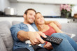 Young Couple Sitting On Sofa Watching Television