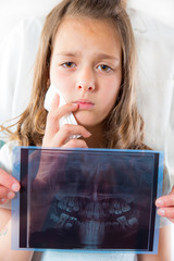 Girl with toothache,  female doctor holding x-ray of teeth