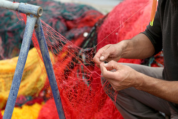 Fisherman Repairs Fishing Net