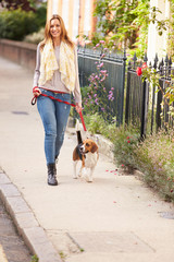 Woman Taking Dog For Walk On City Street